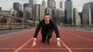 Ejecutivo-con-traje-agachado-en-una-pista-de-atletismo-619x346